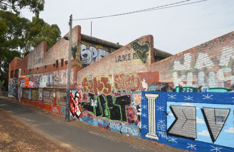 row of old brick buildings with diagonal rooflines covered with graffiti beside a bike path near Jewell train station