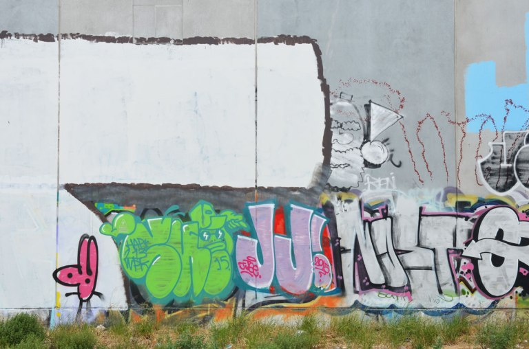 grey concrete wall with graffiti on it, large JJ in pink, a man's head, a green tag, railway tracks are in the foreground.