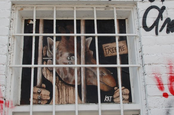 poster of anthromorphic creature with animal mask on, giraffe behind bars. only the head shows in the window. hands are grasping onto the bars.