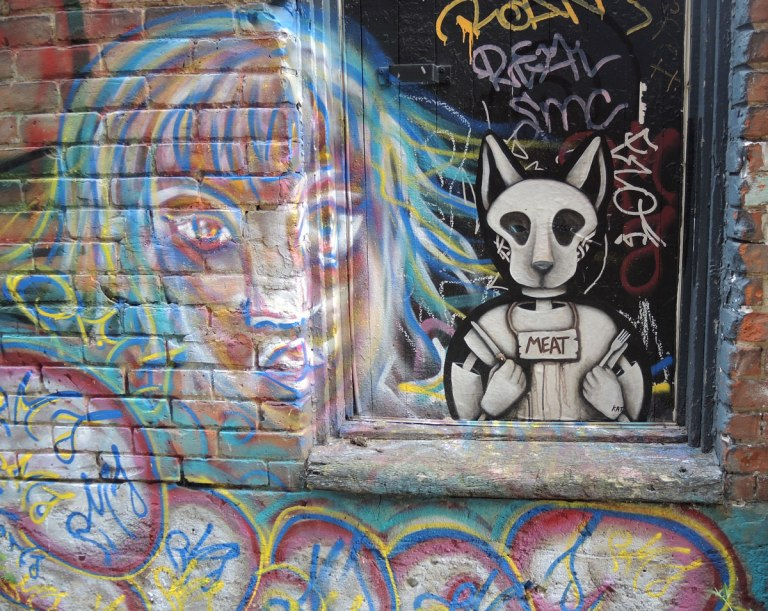 a poster of an creature wearing an animal mask sitting ina window sill, a knife in one hand and a fork in the other, looking like they are ready for dinner. A sign around its neck says 'meat'. A graffiti painting of a woman's face is beside the poster.