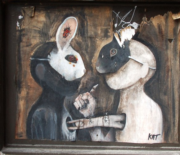 poster of anthromorphic creature with animal mask on - two rabbits, one black mask and one white mask, they are facing each other. A human figure is diving horizontally from a hole in the white creature (who is wearing the black mask) into a hole in the black creature