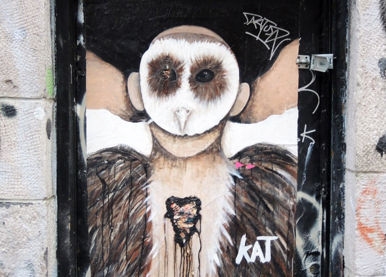 poster of anthromorphic creature with animal mask on, owl mask, with bleeding heart on its chest, and furry feather like coat