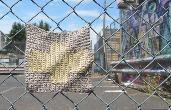 knitted square attached to a chain link fence, beige cross on grey background. Wall of graffiti out of focus in the background.