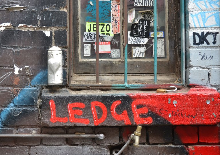 under a window in an alley. the window has metal bars. on the ledge under the window someone has spray painted in large red letters the word ledge