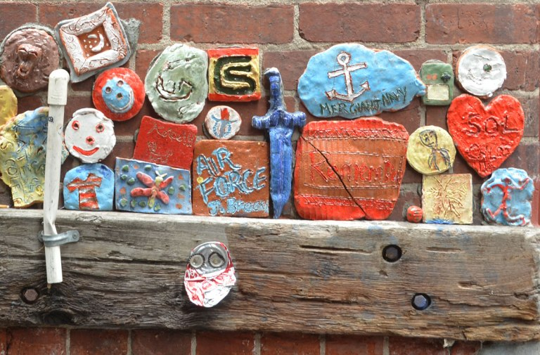 many clay pieces, a sword,an anchor, some with words, attached to a wall, part of a Legacy project for ANZAC commemoration