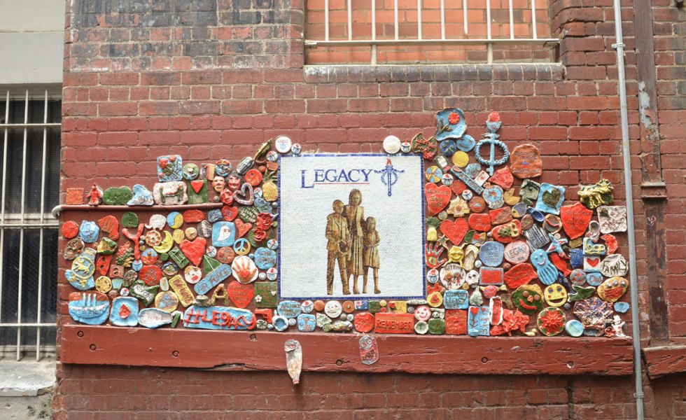 white square tile with the word legacy and a picture of three people, attached to an exterior wall with numerous small clay pieces around it.