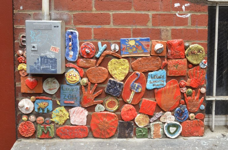 many clay pieces, a hand, some with words, attached to a wall, part of a Legacy project for ANZAC commemoration
