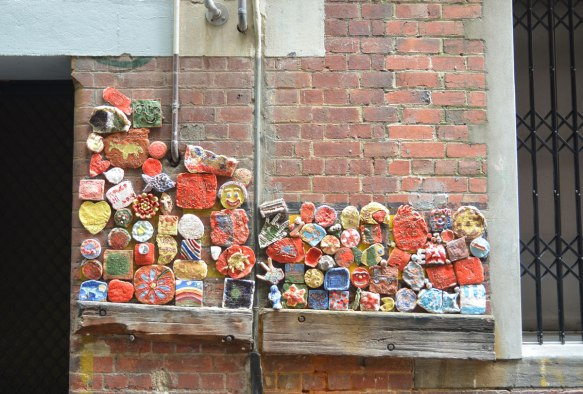 clay pieces on a red brick wall in an alley all clustered together to form a mosaic