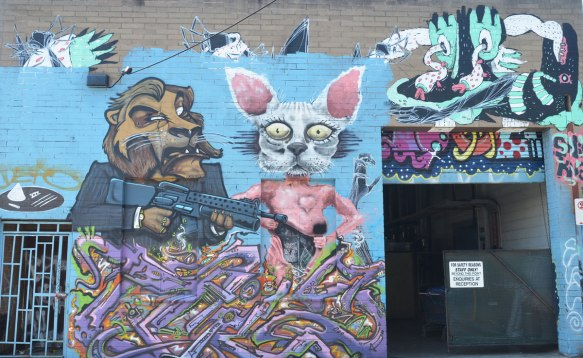 mural of lion (person's body, lion's head) holding a machine gun and standing beside a person with a white rabbit head and pink ears