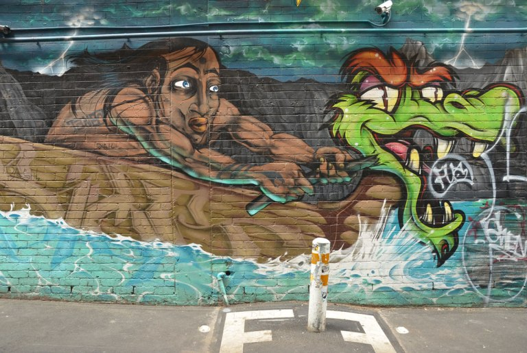 a mural by Sigma 80 in Drewery Lane Melbourne, a brown man in a brown boat that has a head of a dragon at the bow The dragon looks alive and it is turning its head slightly backwards to look at the man