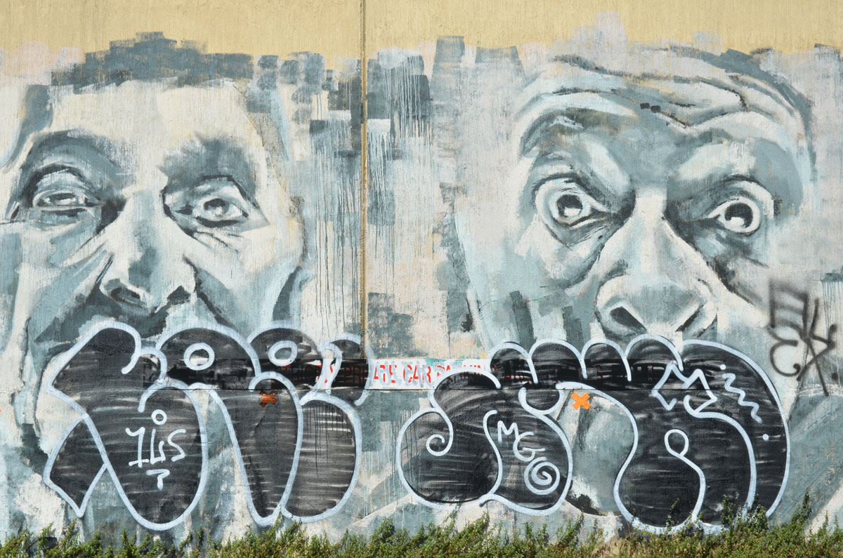 mural of two men's faces in grey tones, with tags on the bottom portion