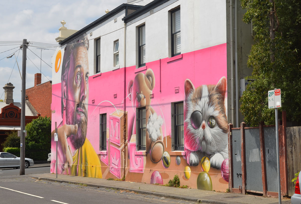view of a mural by smug on Wood street in Melbourne, pink background, a man, a teddy bear and a kitten along with some wooden blocks and some marbles.