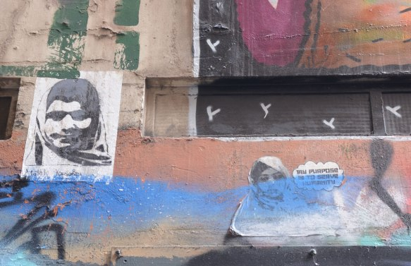 Two wheatpaste pictures of women. On the left is a woman in a head scarf with the name Malala Yousafai written below. On the right is another woman in a head scarf and a thought bubble that says 'My purpose is to serve humanity'.