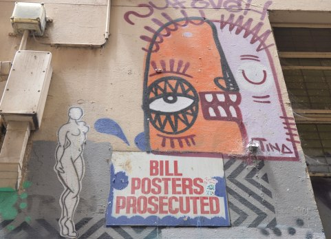 "a wall in a laneway in Melbourne, on it are three things, a sign that says ""Bill Posters Prosecuted"", a paper wheatpaste of a silhouette of a naked woman, and a face in two colours - orange on one side and white on the other, with the name Tina written on it. The orange side has eye open and the white side has eye closed."