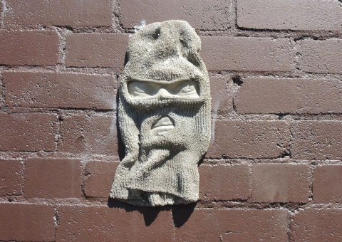 balaclava mounted on a brown brick wall, spray painted gray