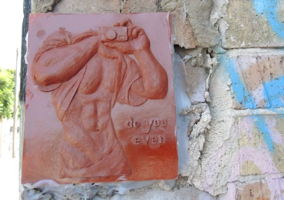 small relief sculpture graffiti of a headless man holding up his T-shirt while holding a camera. Great abs on the guy