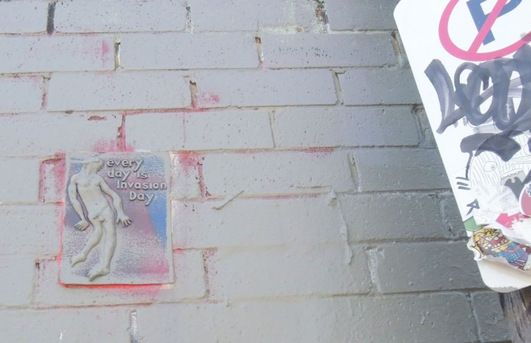 small relief sculpture graffiti of a naked man with the words 'Every day is invasion day'