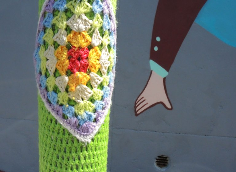 pole wrapped in colourful yarn crocheted in square pattern, laid on point, with green crochet yarn around the diamonds.