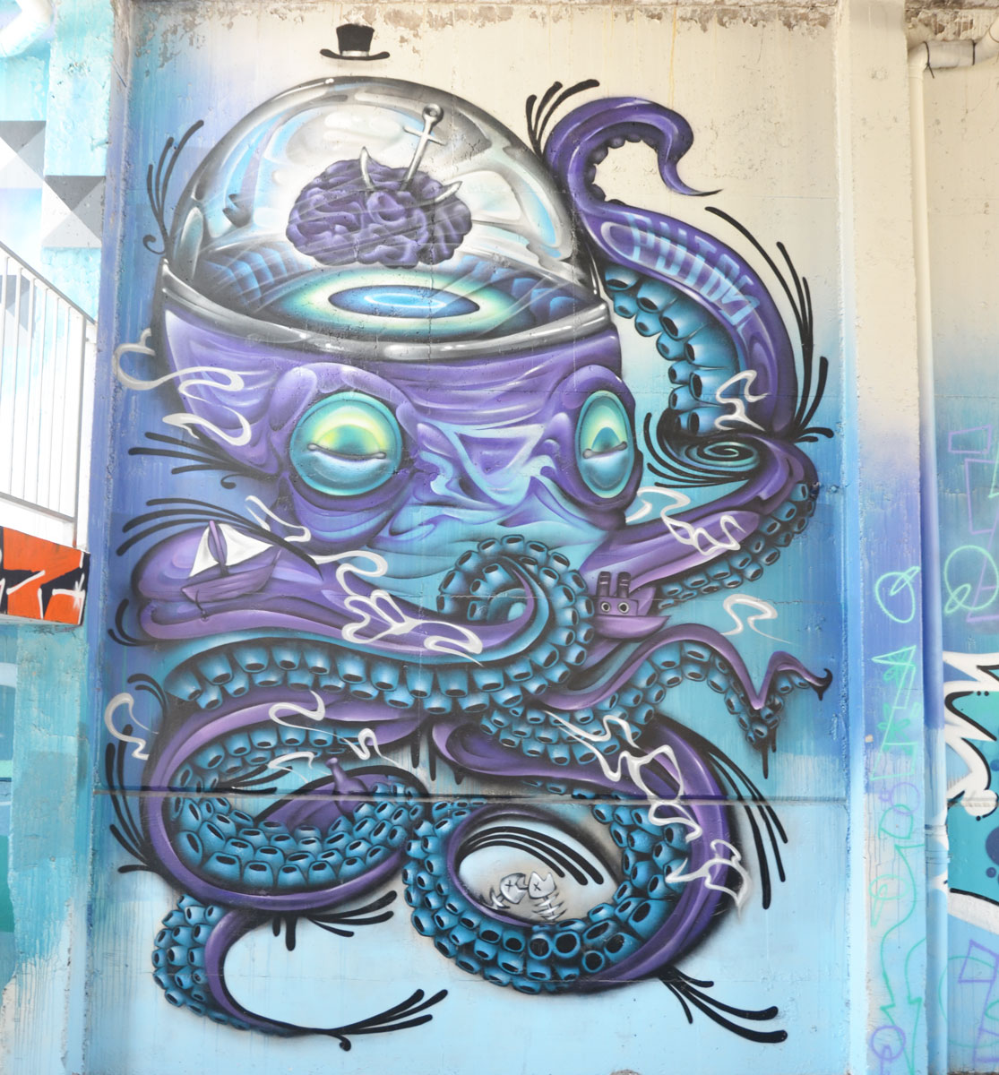 a street art painting of a blue and purple octapus. It's wearing a tiny little black top hat