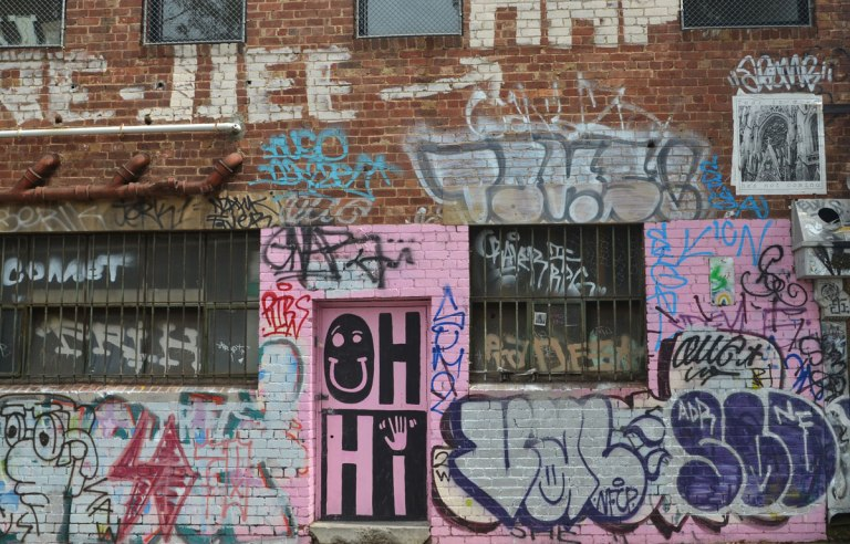 A lot of graffiti on a red brick wall. A door is in the middle and it has been painted pink. large black and pink letters are painted in it that say Oh Hi. The O in Oh is a happy face. The i in Hi is an arm and hand.