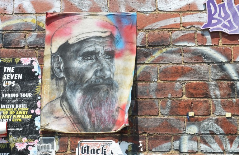 A drawing of an older man with a beard, wearing a white hat, on a piece of paper attached to a brick wall