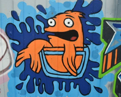 a street art painting of an orange fish (not realistic looking) sitting in a glass bowl, with a surprised expression on its face