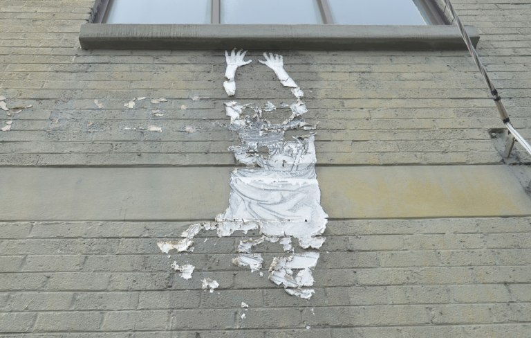 paper graffiti of a person hanging from a window sill (which is real), person is paper. It has started peeling away