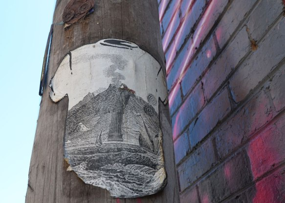 High on a pole, a paste-up of a white T-shirt on which there is a large black and white a detailed bdrawing