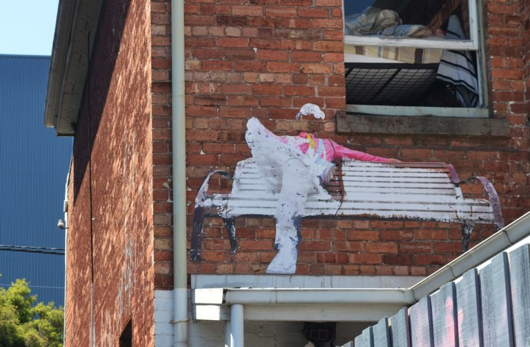 on a red brick wall, at second storey level, a large paste-up of a white wood bench with a person sitting on it. The person is wearing white trousers and shoes and a pink shirt.