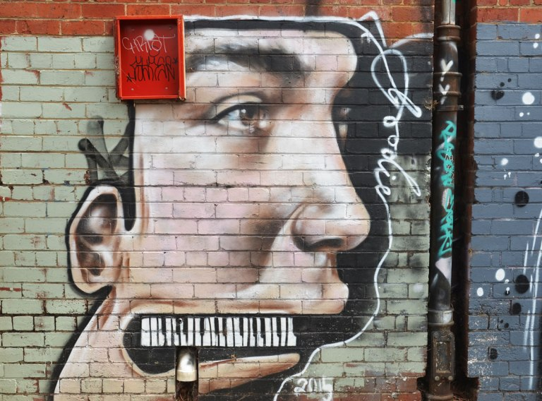 street art painting of a young man's face in profile, instead of teeth he has a piano keyboard