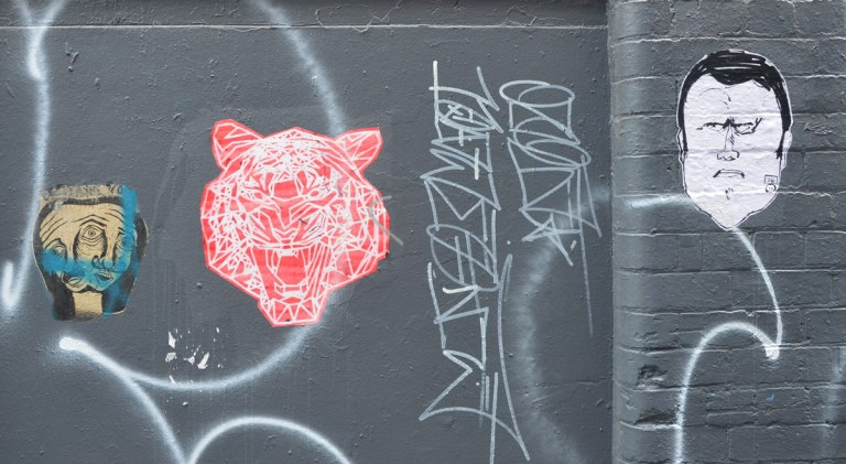 three paste ups, wheatpastes, on a black wall in an alley in central Melbourne. On the right is a man's head (black on white paper), in the middle is a pink tiger head with its mouth wide open and on the left is a head that looks like two heads merged together