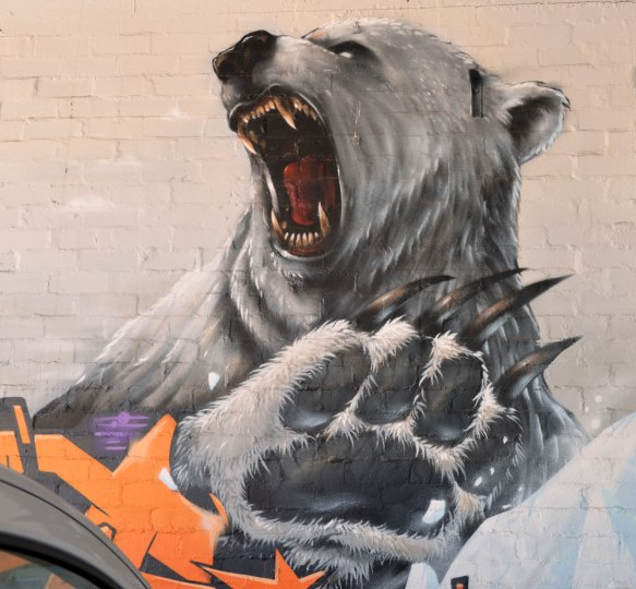 head and paw of a polar bear painted on a wall. The bear is roaring, it has it's mouth wide open and his teeth are showing.