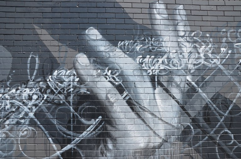 monochromatic painting in  greys of a hand on a large mural