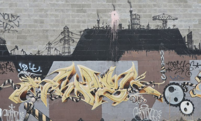 mural with symbols of industry, gears, power line, smoke stacks,