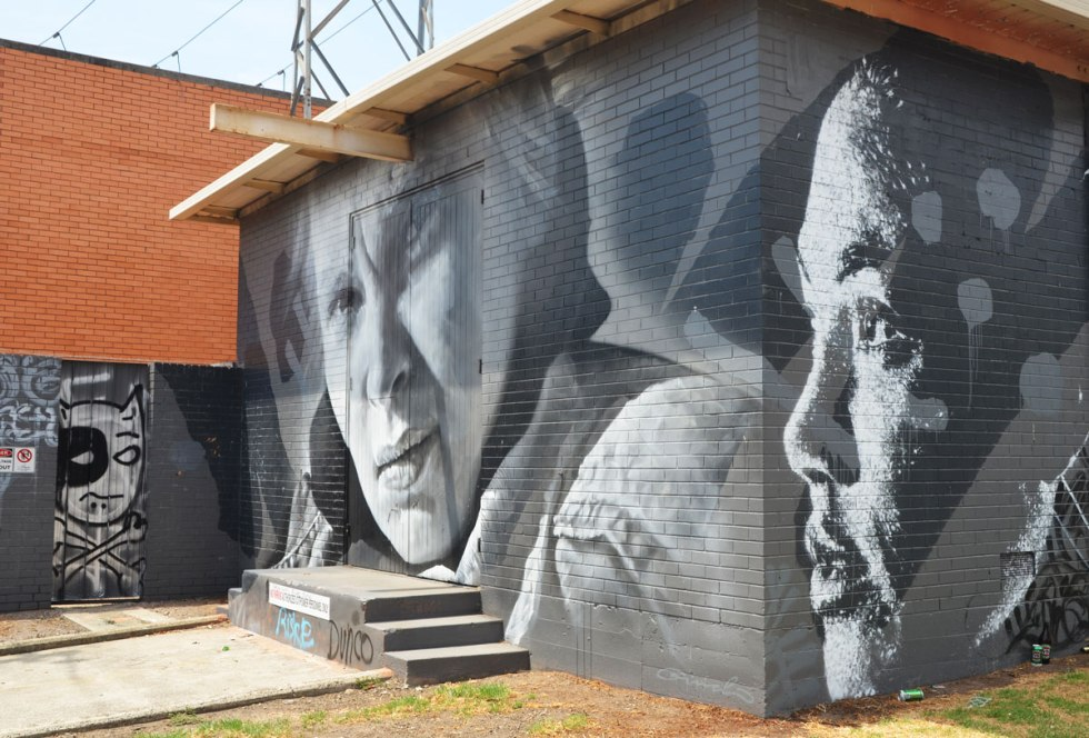monochromatic realistic portrait of two women part of a larger mural painted on a wall surrounding a power substation in Melbourne