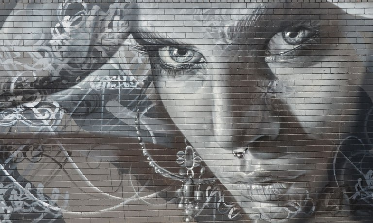 monochromatic realistic portrait of a woman part of a larger mural painted on a wall surrounding a power substation in Melbourne.  The woman has a ring in her nose