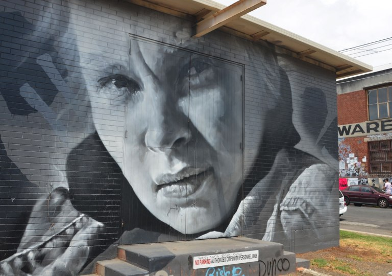 monochromatic realistic portrait of a woman part of a larger mural painted on a wall surrounding a power substation in Melbourne