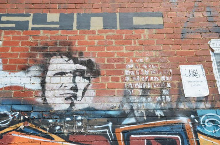 graffiti on a brick wall, sync written in large block black letters, a black outlined white face, and a poster that says professional loser.