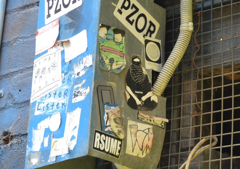 Many slaps and stickers on a metal box in an alley. Stickers with Pzor written on them and sticker saying Rsume. A picture of a person in black robes and a veil.