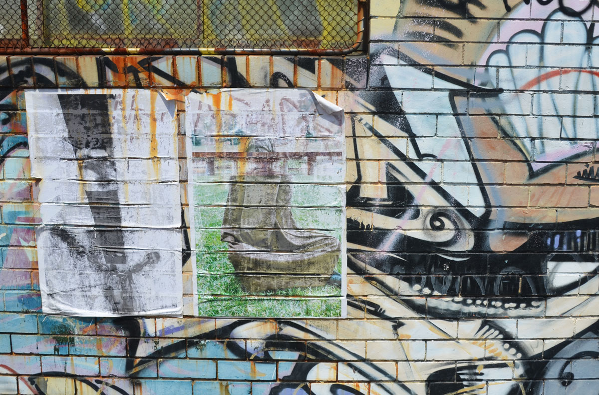 two worn and faded posters on a graffiti covered wall