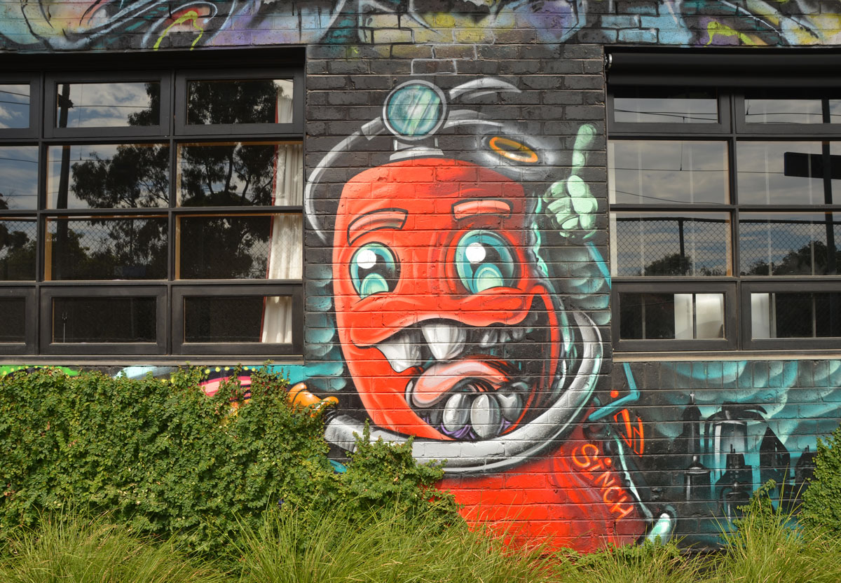 cartoon painting of a red fire hydrant (or maybe fire extinguisher) with a big mouth, several teeth, and a tongue, two eyes, and hoses for arms.