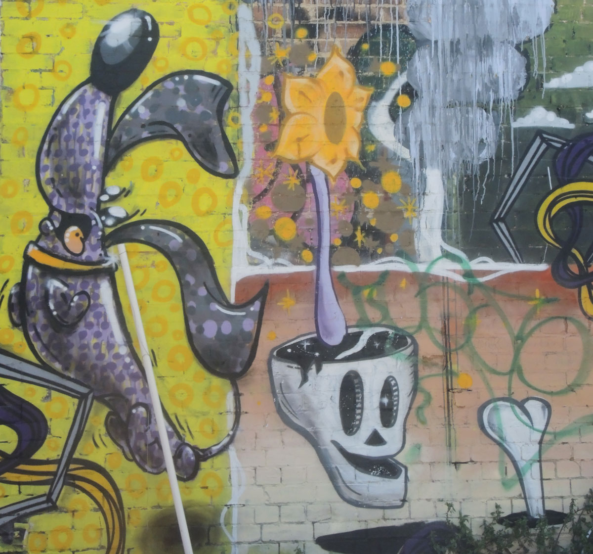 part of a larger mural with a skull, a bone in a hole and a sunflower growing out of the top of the skull