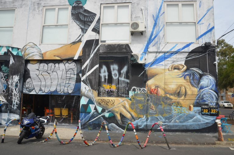 mural on the side of a two storey building of a woman lying on her side. A black bird is sitting on her shoulder. There is a yarn covered bike rack in front