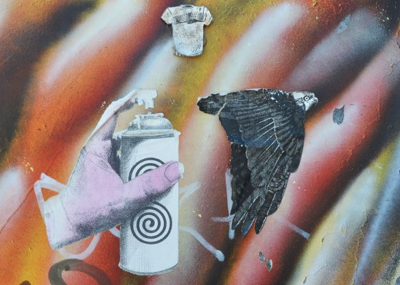 three paste ups on a wall with striped spray paint, white, black, red and gold. Small T-shirt, an eagle in flight, and a pink hand holding onto a spray paint can. It looks like the spray is aimed at the eagle.