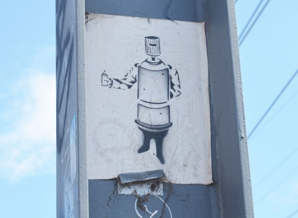small wheatpaste poster on a metel support. The picture is of a spray paint can made to look like a person. The top (where you push down) is the head. Cylinder shaped body. It has two arms and it is holding a small spray can in one hand.