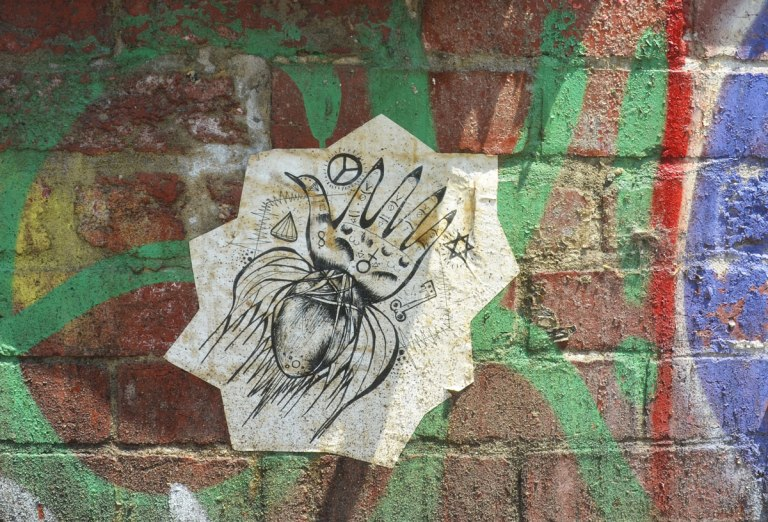wheatpaste, black on white, graffiti on a brick wall that has some green spray paint on it, drawing is of a squid with a head that looks like a hand with five fingers. there are other symbols on it too, a peace sign, a key, a star of David, a diamond, the symbol that equals female
