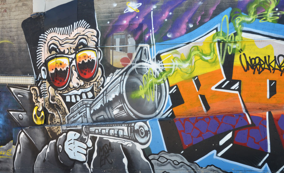street art painting of a man holding a large gun pointing at the viewer
