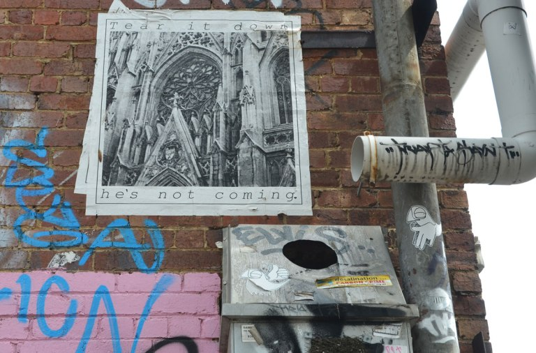 "poster graffiti high on a wall of a picture of a cathedral with the words ""Tear it down. He's not coming"""