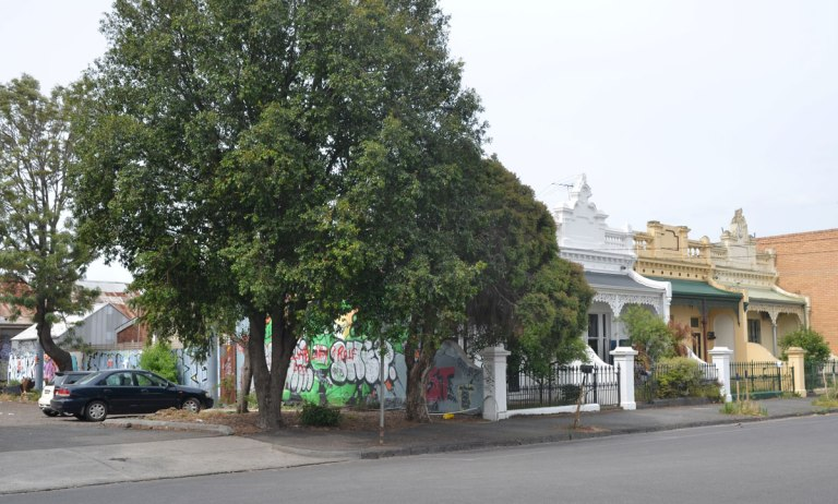 a row of terrace houses in Brunswick Melbourne with a parking lot at the left side. The side of the house closest to the car park has a mural painted on it.