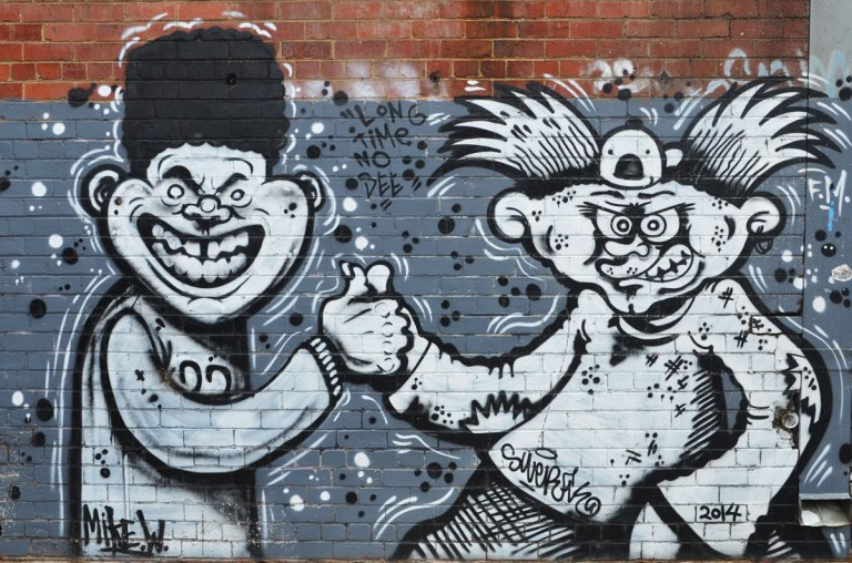 street art painting in grey tones of two guys meeting, thumbs together, both with silly grins on their faces. One has black afro hair and the other has long stick up in the air hair.